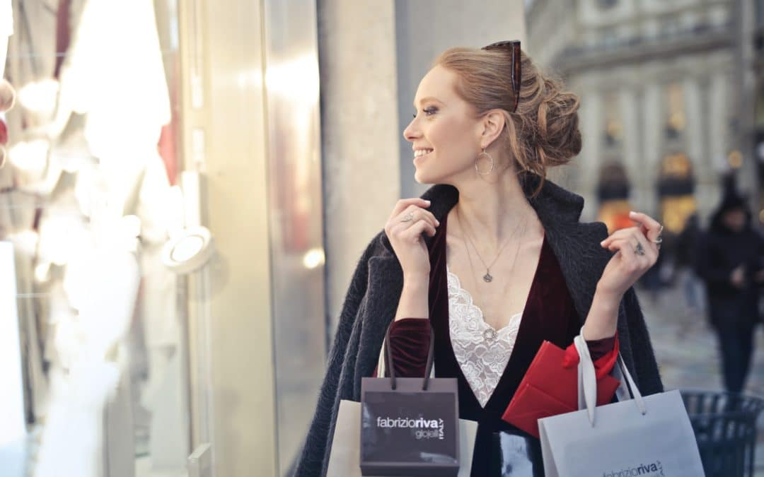 A customer looking at a shop front window holding shopping bags.